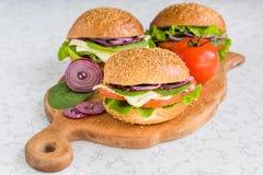 Burgers met groenten en kaas op scherpe raad Royalty-vrije Stock Afbeeldingen