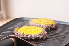 Burgers with mustard. Burgers cooking on a grillpan with mustard on top Royalty Free Stock Image