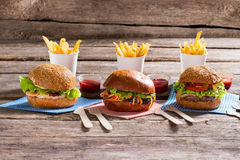 Burgers on napkins with cutlery. Royalty Free Stock Photo