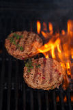 Burgers on party summer barbecue grill with flame Royalty Free Stock Photography