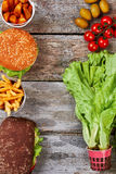 Burgers and raw vegetables. royalty free stock photography