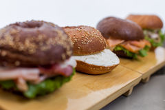 Burgers with sauce on wooden plank on bread background. Burgers with sauce on wooden plank on other burgers background close view stock photos