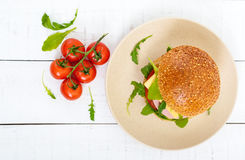 Burgers with sausage, cheese, tomato, arugula and soft bun with sesame seeds Royalty Free Stock Image