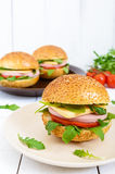 Burgers with sausage, cheese, tomato, arugula and soft bun with sesame seeds on a white wooden background. Stock Photos