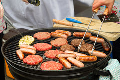 Burgers and sausages on barbecue. Fire Stock Image