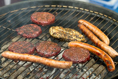 Burgers and sausages on barbecue Royalty Free Stock Photo