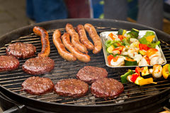 Burgers and sausages on barbecue Stock Photos