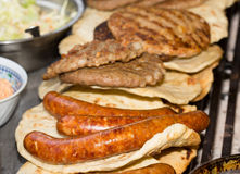Burgers and sausages on barbecue. Group of grilled sausages and burgers on tortillas. Traditional balkan barbeque fast food Stock Photos