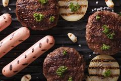 Burgers and sausages with grilled vegetables macro top view Stock Photos