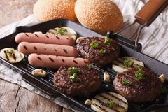 Burgers and sausages with vegetables on a grill pan, horizontal Stock Images