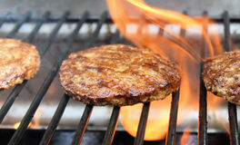Burgers Sizzling On The Grill Stock Image