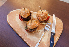 Burgers Sliders. Three Burgers Sliders On Rustic Wooden Plate Stock Photography