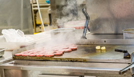Burgers Smoking on Griddle. In commercial Kitchen Royalty Free Stock Photo