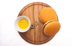 Burgers on the white background and wooden table. Home made delicious burgers with grilled beef and cheese served with mustard, Italian spices and herbs on a Stock Images