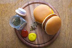 Burgers on a wooden table. Home made delicious burgers with grilled beef and cheese served with ketchup, mustard and Italian spices and herbs on a wooden table Stock Photo