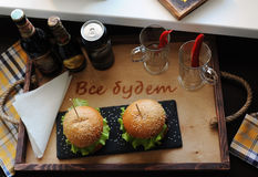 Burgers on a wooden tray. Beer glasses on served table. The atmosphere is fun. For two Royalty Free Stock Images