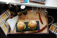 Burgers on a wooden tray. Beer glasses on served table. The atmosphere is fun. For two Stock Photo