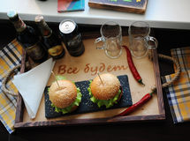 Burgers on a wooden tray. Beer glasses on served table. The atmosphere is fun. For two Royalty Free Stock Photo