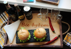 Burgers on a wooden tray. Beer glasses on served table. The atmosphere is fun. For two Stock Image