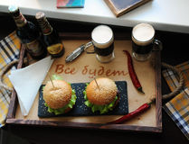 Burgers on a wooden tray. Beer glasses on served table. The atmosphere is fun. For two Stock Photos