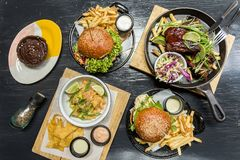 Burgersm french fries, ceviche, ribs and muffin on a wooden table royalty free stock photos