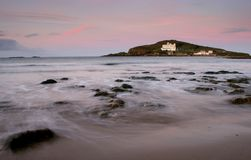 Burgh Island at Sunrise. Burgh Island off the Devon coast basks in the early morning sun as the tide rises to cut it off from the mainland. The hotel is of a Art Stock Photography