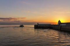 Burghead, bateau partant au coucher du soleil. Photo stock