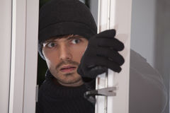 Burglar. With crowbar breaking into a house through glass door Stock Images