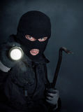Burglar. In black balaclava with crowbar and flashlight at night Royalty Free Stock Photography