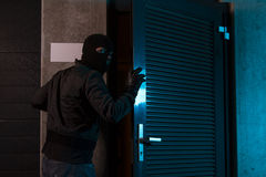 Burglar. Wearing balaclava opening door Stock Photo