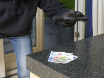 Burglar in action. Burglar enters a kitchen to grab money from the kitchen counter stock image