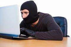 Burglar with balaclava hacking a laptop Royalty Free Stock Image