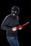 Burglar with balaclava. A burglar wearing a balaclava holding huge wire cutters over black background stock photos