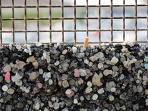 Burglar bars and rubbish pile. Photo closeup of aged white rusty metal grating burglar bars and chewing gums curbstone rubbish pile on blurred background stock image