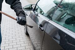 Burglar with crowbar and gloves try open car royalty free stock photo