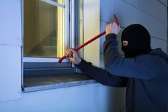 Burglar Using Crowbar To Break Into A House. Burglar With Black Mask Using Crowbar To Break Into A House At Night Stock Image