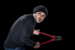Burglar in black. A burglar wearing black clothes holding huge wire cutters over black background stock images