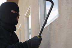 Burglar Breaking Into House. Burglar wearing a ski mask with crowbar breaking into a house stock photo