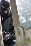 Burglar Breaking Into House. Burglar with crowbar breaking into a house through door stock images