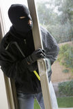 Burglar Breaking Into House. Burglar with crowbar breaking into a house royalty free stock image