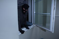 Burglar Breaking Into A House. Burglar Wearing Balaclava Breaking Into A House Through The Window Royalty Free Stock Photo