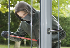 Burglar breaking in a house. Burglar wearing black clothes and leather coat breaking in a house Stock Photos