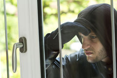Burglar breaking in a house. Burglar wearing black clothes and leather coat breaking in a house Stock Image