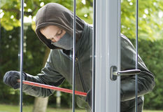 Burglar breaking in a house Stock Images