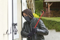 Burglar breaking in a house Royalty Free Stock Photography