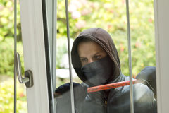 Burglar breaking in a house. Burglar wearing black clothes and leather coat breaking in a house Royalty Free Stock Photos