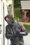 Burglar breaking in a house Stock Photos