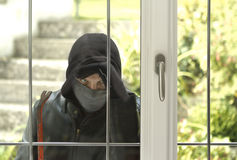 Burglar breaking in a house. Burglar wearing black clothes and leather coat breaking in a house Royalty Free Stock Photo