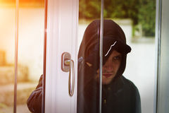 Burglar breaking in a house. Burglar wearing black clothes and leather coat breaking in a house Royalty Free Stock Images