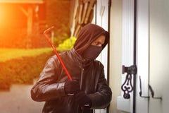 Burglar breaking in a house Stock Photo